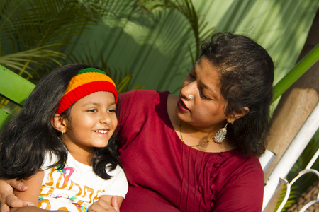 Small Indian girl and her mother chatting with each other while sitting in a garden, Pune