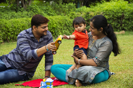 Happy Indian family, father giving toy car to his toddler son, sitting with his mother, inside garden, Pune, Maharashtra