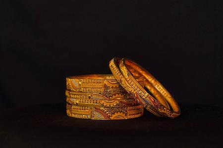 Künstliche goldene Armreifen hautnah auf schwarzem Hintergrund