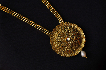 Artificial golden necklace on a black background Фото со стока
