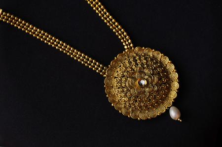 Künstliche goldene Halskette auf schwarzem Hintergrund Standard-Bild