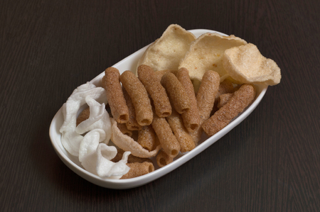 Close-up of variety snacks plate on wooden table.