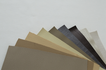 Leather sheet stack of gray and brown color shades on white background.