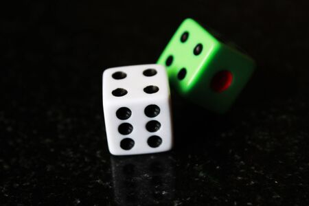 Two dice on a black background, game play