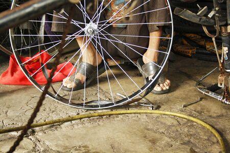 Man repairing bicycle at Ratan cycle mart in Mandai, Pune, India.