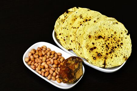 Roasted papad an Indian snack with whole peanuts and jaggery in a plate. Imagens