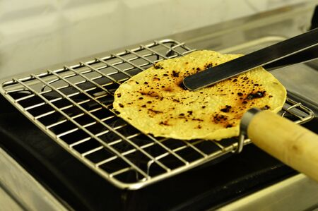 Papad an Indian snack being roasted on a gas stove. Stock Photo