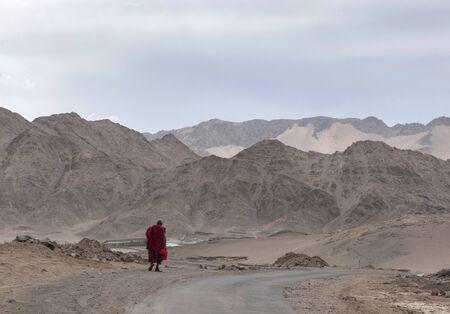 Monk walking with mountain backdrop at Ladakh, India Stock Photo
