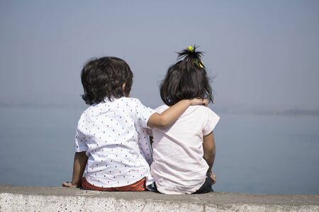 Boy and little girl sitting near lake at Veer dam in Pune, Maharashtra, India. Banque d'images - 132046572