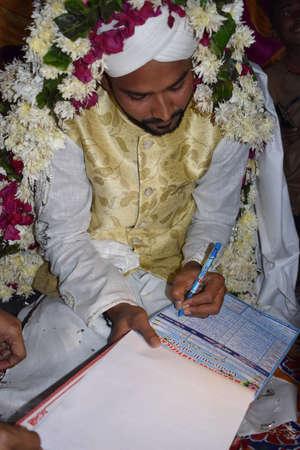 Indian Muslim groom signing the nikah nama or marriage contract an Islamic prenuptial agreement at Ahmedabad, Gujarat