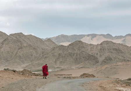 Monk walking on road with mountain landscape, Ladakh, India 新闻类图片