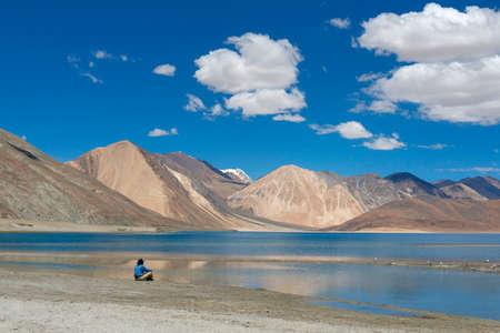 Tourist at Pangong lake, Ladakh, India. Pangong Tso is an endorheic lake in the Himalayas situated at an elevation of 4,225 m