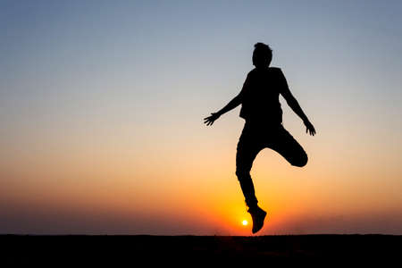 10 Nov 2020 Thar desert, Jaisalmer, Rajasthan, India. Silouette  of a boy jumping on sand while sun setting in background Editorial