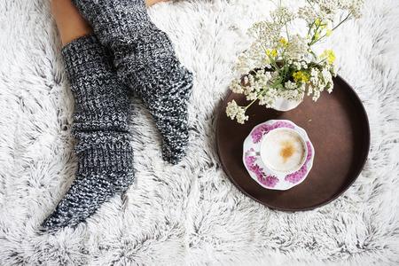gambe della ragazza in calze di lana caldi e una tazza di caffè riscaldamento, mattina d'inverno a casa