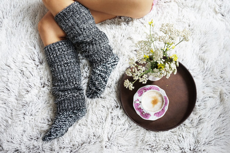 legs of girl in warm woolen socks and a cup of coffee warming, winter morning at home