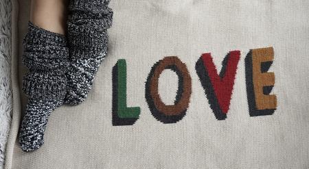 legwarmers: legs of girl in warm woolen socks on a Love blanket, winter morning at home Stock Photo