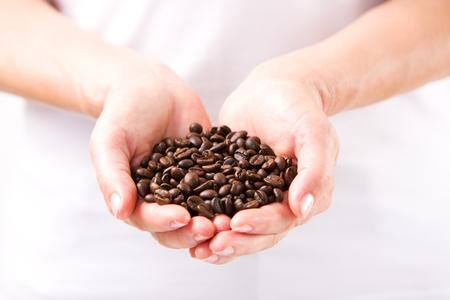 Granos de café en manos femeninas Foto de archivo - 100129246