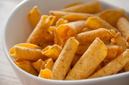 titbits: cheese potato chips in white bowl on wooden table Stock Photo