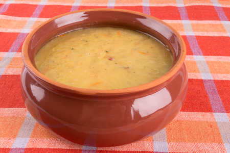 Traditional fresh pea soup in a bowl on a tablecloth photo