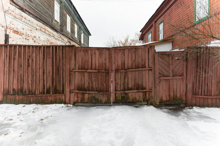 very old wooden gate on the street photo