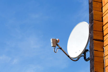 telecast: Satellite antenna on the wall of a wooden house