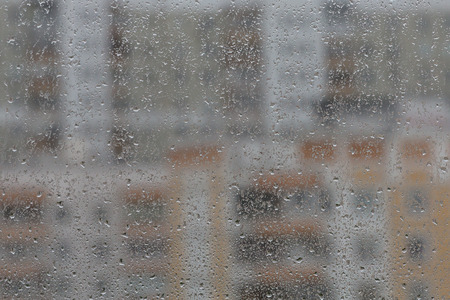 window pane: Drops of rain on a window pane, buildings in background Stock Photo