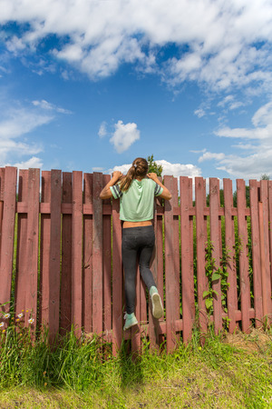 prying: Girl peeking through the fence on a sunny day