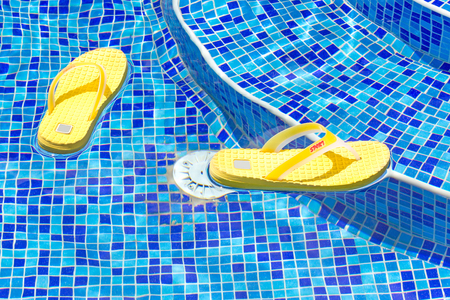 swim shoes: flip-flops floating in a swimming pool Stock Photo