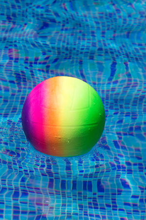 furlough: colorful ball floating in a pool
