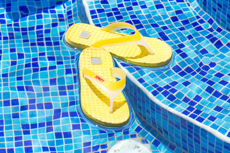 swimming shoes: flip-flops floating in a swimming pool Stock Photo
