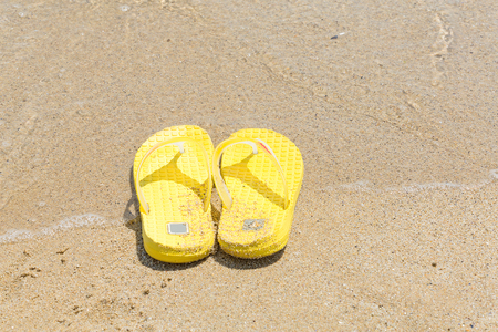 swim shoes: flip-flops on the shore of the beach in the sand