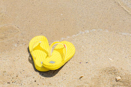 swimming shoes: flip-flops on the shore of the beach in the sand