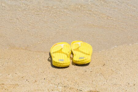flipflops: flip-flops on the shore of the beach in the sand