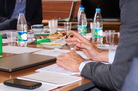 negotiating: man gesturing at the negotiating table