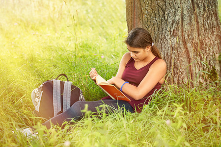 The girl is reading a book by the tree Standard-Bild