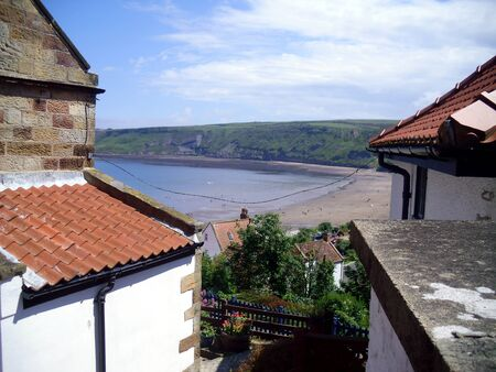 north yorkshire: View of Runswick Bay in North Yorkshire Through the Rooftops Stock Photo