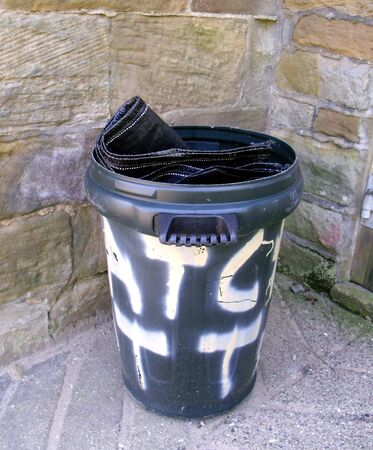 Black Plastic Bin with white graffiti with a Stone Wall in the Background Stock Photo - 61107008