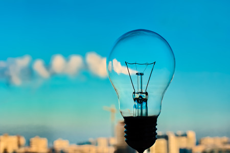 incandescence: The incandescence bulb by the industrial city background Stock Photo