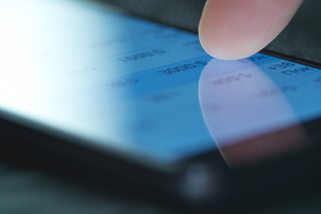 finance report: The hand (finger) work with phone touchscreen