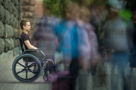 The invalid man sit in the wheel chair in the crowd stream at sidewalk
