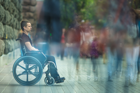 motionless: The invalid man sit in the wheel chair in the crowd stream at sidewalk