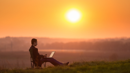 business backgound: The man sit and work on the laptop by sunset (sunrise) background on the top of the hill