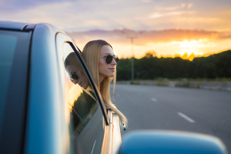 The girl in the car against the background of a road and picturesque sunset