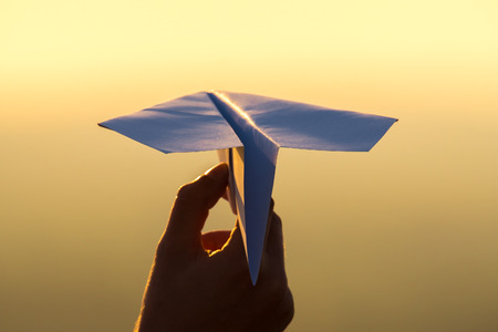 The hand hold paper airplane and launch on the background of picturesque sunset