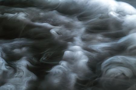 unusually: The stream of thick smoke on a dark background