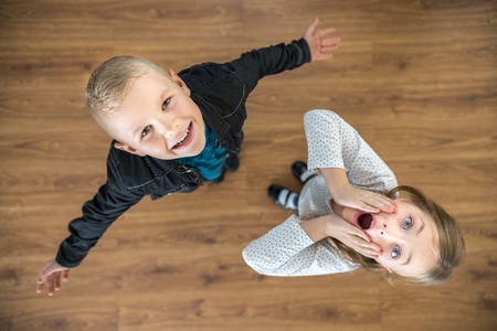 The two surprised children look up. View from above