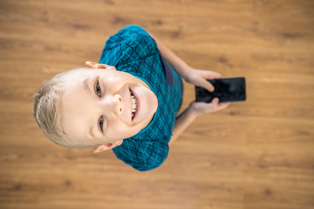 The boy laugh to camera and hold a phone in hands. View from above