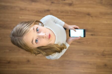 The surprised girl look up and hold a phone in hands. View from above Stock Photo