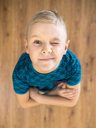 The cute boy gesture and wink to the camera. View from above Stock Photo