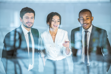 The three business people stand near the window Stock Photo